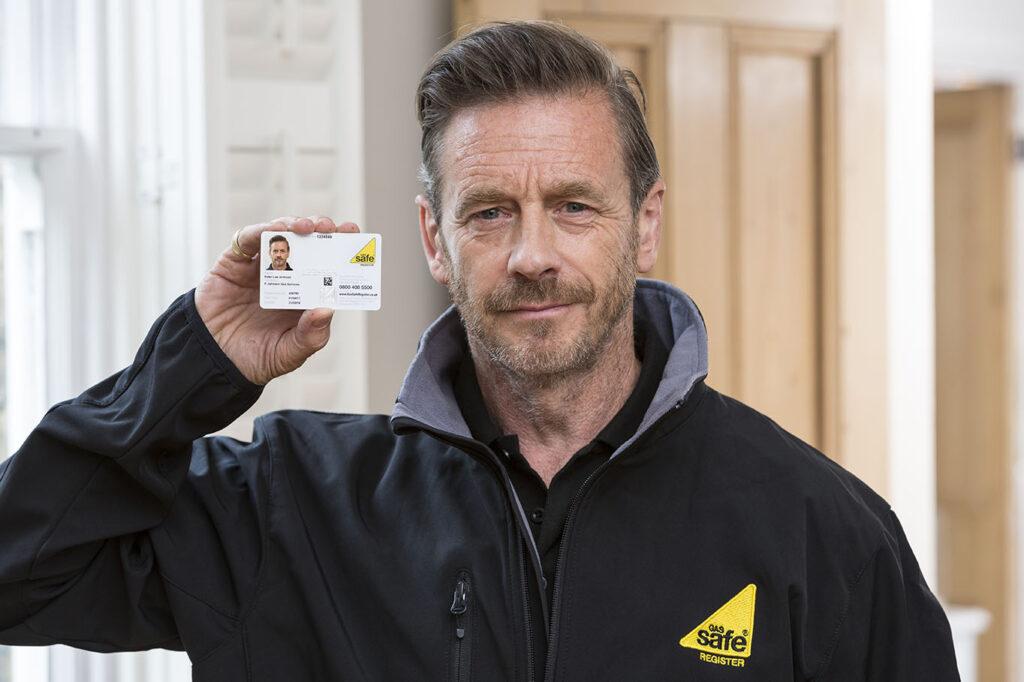 Male engineer displaying Gas Safe ID card.